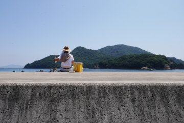 A fisherman trying his luck in the Tomo waters