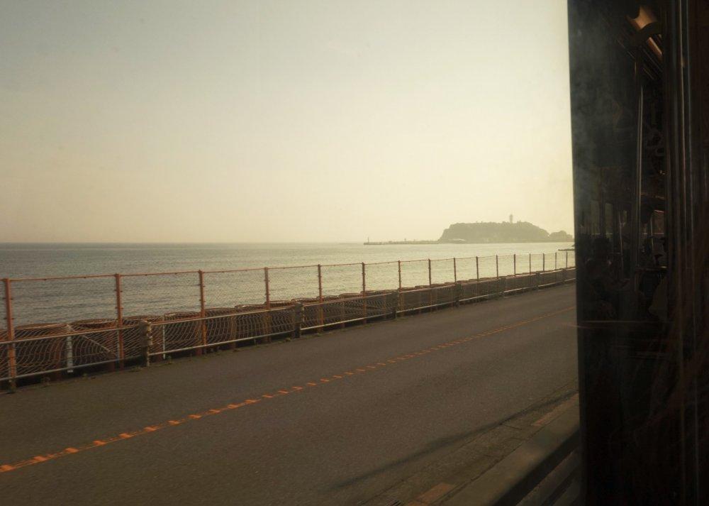 Bạn có thể nhìn thấy hòn đảo Enoshima đang đến gần, khi tôi đang trên tàu Enoden từ Kamakura