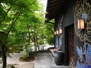 Taman batu dan barisan pohon menunjukkan jalan masuk ke Cafe