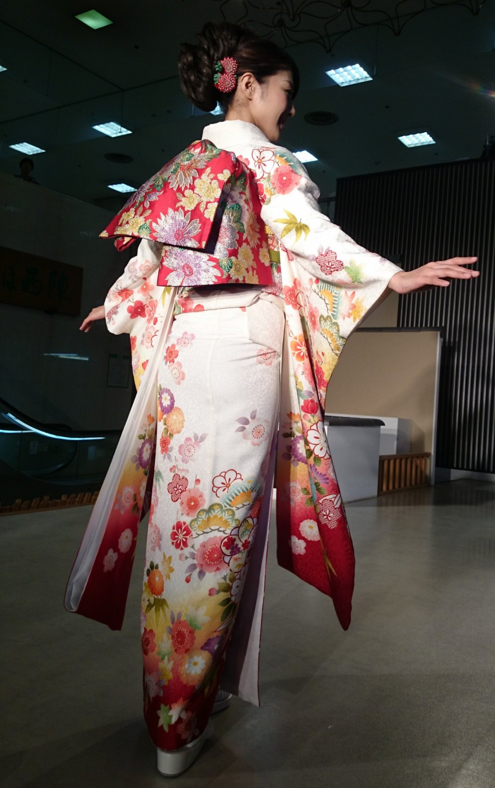 The floral design of the obi (tied at the back) distinctively recalls autumn colors