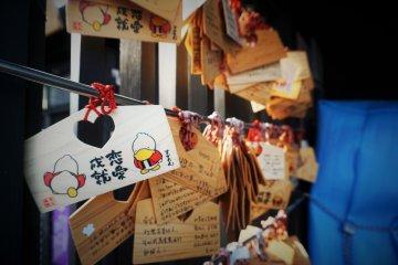 掛著許多祈求戀愛運的繪馬,繪馬上還有巢鴨的吉祥物。