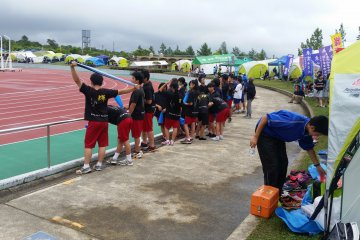 Young athletes watch runners amid a busy group of school tents
