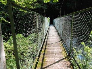Estreita ponte suspensa sobre um rio atravessado pelo trilho