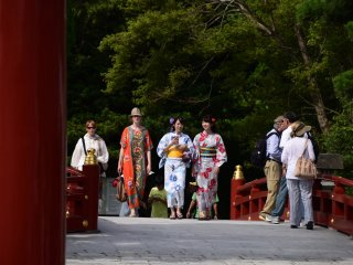 Foreign tourists and Japanese women in yukata were crossing the red bridge that stood next to Taiko-bashi