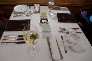 ไวน์บนโต๊ะอาหารค่ำ กับเครื่องอุปกรณ์การรับประทานอาหารแบบฝรั่งที่เรียงเต็มโต๊ะ มีดสี่ ซ๋อมสาม