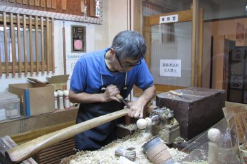 A craft worker transforms a block of wood in to doll