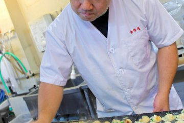 Chef making takoyaki at Aizuya at Tempozan Marketplace. The Palm-Auth-Pay app works here.