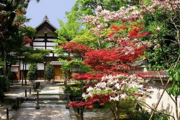 A smaller building on the temple grounds, surrounded by flowers.
