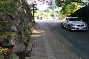 The stone walls to the entrance of the parking lot were once the walls of Nenoman Gate