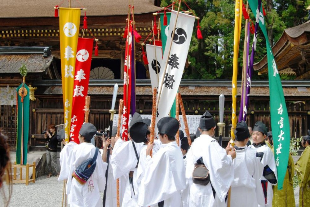 Boys wearing traditional costumes carry the Kumano flags