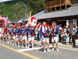 Groups of girls and boys, women and men carry a mikoshi (portable shrine), or in the case of the men, a big sake barrel