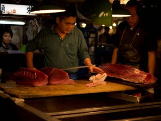 В то время как свежий тунец режется огромными ножами