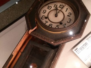 Haunting exhibit of a clock stopped at exactly 11:02.
