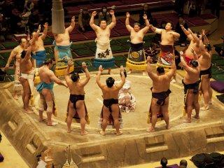 Makuuchi (top division) wrestlers form a circle wearing decorative 'kesho-mawashi' aprons
