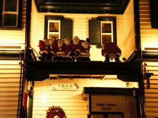 Many Santa Claus assemble on rooftops at night-time