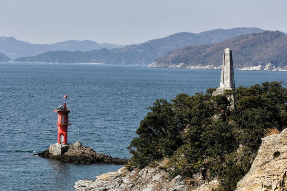 """Ngọn hải đăng và tượng đài ở cuối mũi Suwazaki ở Yawatahama. Trên biển có ghi """"Đừng trèo qua lan can""""."""