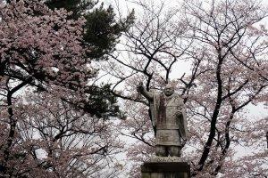 รูปปั้นภายในวัด ยืนเด่นท่ามกลางดอกไม้สีชมพู