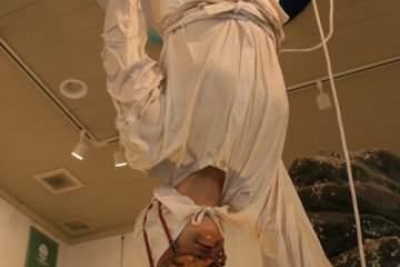 """An Ama San clothed mannequin """"dives"""" from the ceiling"""