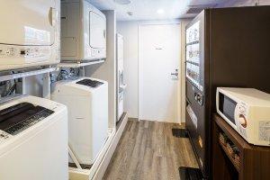 เครื่องซักผ้าและเครื่องอบผ้าหยอดเหรียญ และตู้เครื่องดื่มหยอดเหรียญที่จุเต็มไปด้วยเครื่องดื่มนานาชนิด