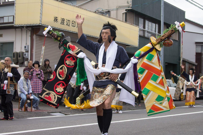 Một vũ công múa kiếm mang chiếc obi trên những cây kiếm gỗ
