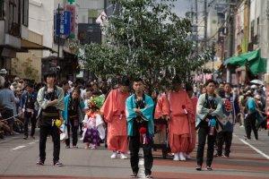 Những người đàn ông mặc chiếc áo choàng của lễ hội đi trước các linh mục