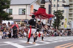 Người biểu diễn tung một cây cột khổng lồ trong đám rước