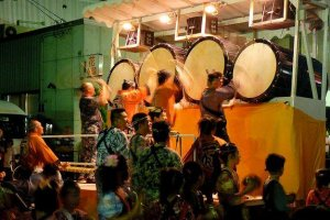 Pulled and pushed between the floats, drummers in traditional garb provide background music for the festival.