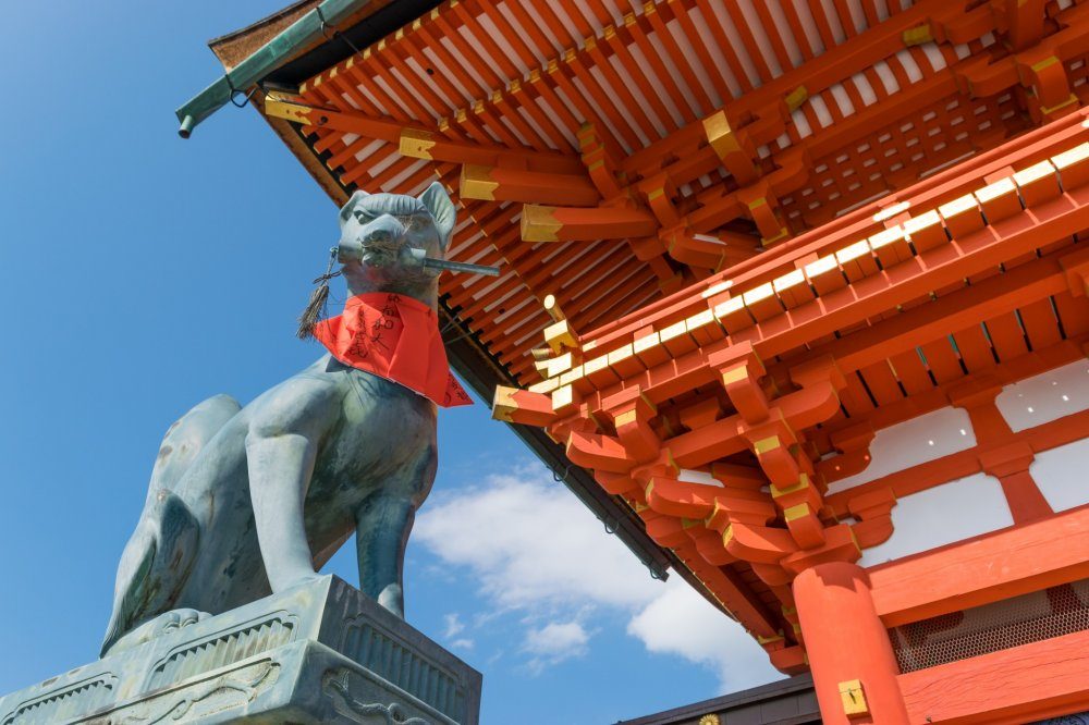 An effigy of Kitsune overlooking visitors to Fushimi Inari-taisha, Kyoto.