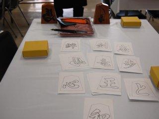 Chuẩn bị sẵn sàng: quân cờ shogi, mực đen và cọ và những bản sao của ký tự kanji là những thứ cần thiết để sơn quân cờ shogi ở Tháp Tendo Shogimura tại Thị trấn Tendo, quê hương của cờ shogi Nhật Bản