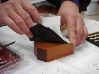 Trước hết đặt một bản sao ký tự bạn chọn và một miếng giấy than lên quân cờ shogi bằng gỗ - Thị trấn Tendo, quê hương của cờ shogi Nhật Bản