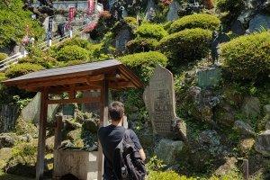 รูปแกะสลักหินคะระซุ-เท็งงุ และป้ายหินที่มีชื่อของผู้บริจาคเงินให้แก่วัดเค็นโชะ-จิ