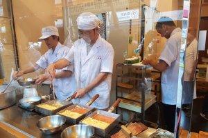 ยืนมุงดูวิธีการทำ 'ทะมะโกะยะกิ' (tamagoyaki) ไข่หวานเสียบไม้แบบญี่ปุ่นแท้