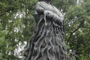 Estátua de mulher com vestes de água, simbolizando o ribeiro de Urakami onde muitos procuraram saciar a sede e acalmar a dor das queimaduras, acabando por perecer. Esta estátua carrega as vítimas com carinho, trazendo paz a quem a observa, e ajudando a fazer o luto.