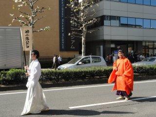 """Antes de uma personagem histórica em particular podemos ver um assistente com a bandeira que refere a personagem. É um desfile de """"celebridades"""" da história do Japão!"""