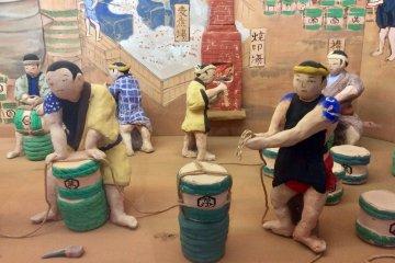 Диорама изображает процесс изготовления соевого соуса в городе Нода в период Эдо