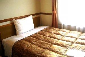 Orange Standard Issue Bed Sheets in the single room in Toyoko Inn Juso