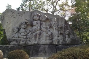 A large stone mural of children at the base of the observation hill