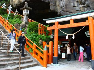 Make your way carefully down a flight of stone steps to the shrine entrance, marked by a red torii in the mouth of the cave.