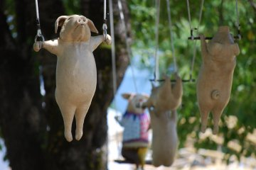 """The animals from """"Circus"""" by Tomio Okayama are suspended in trees at the park"""