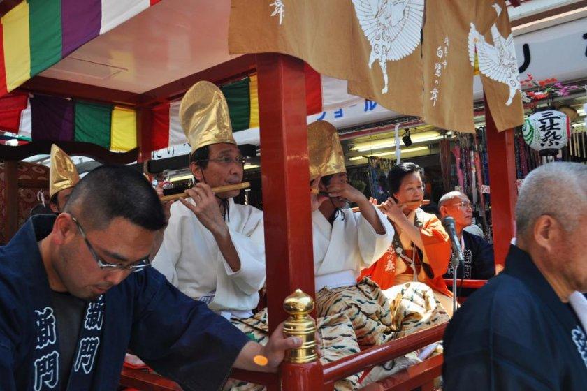 Para musisi sedang memainkan instrumen tradisional mereka