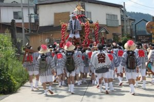 """On the 9th, men in their """"yaku"""" (bad luck) years, shake off their hangovers and carry a heavy """"Omikoshi"""" through the village."""