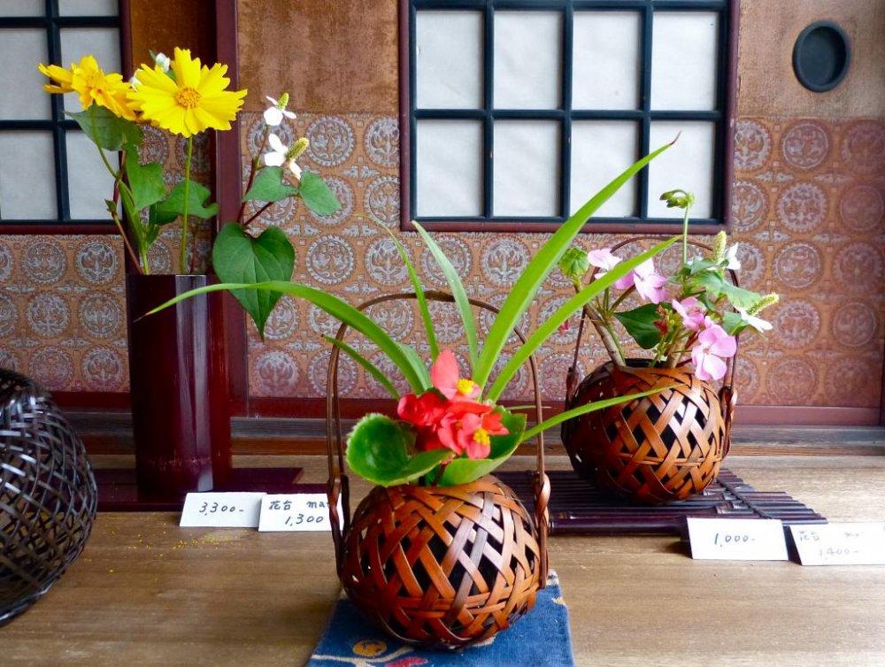 Bunga-bunga kecil ditata dengan sederhana di dalam keranjang-keranjang berwarna oranye tua