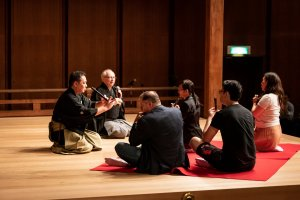 """Noh musician explains to the volunteers how to play """"fue"""", the flute"""