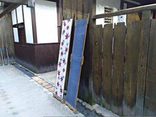 """Nas traseiras dos armazéns dos mercadores de Osaka podem ver-se panos a secar, encostados às vedações. Ao longo destas """"ruas de trás"""" há canais de escoamento de água."""