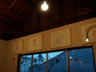 นกนางแอ่นกระดาษแขวนประดับบนหน้างต่าง และมีภาพวาดสีสันสดใสวางเรียงบนผนัง