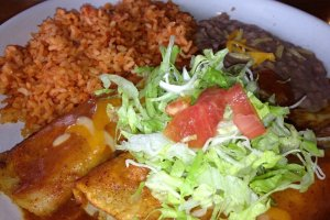 The enchilada plate is a bit spicy and comes with three enchiladas topped with lettuce, refried beans, and Mexican rice