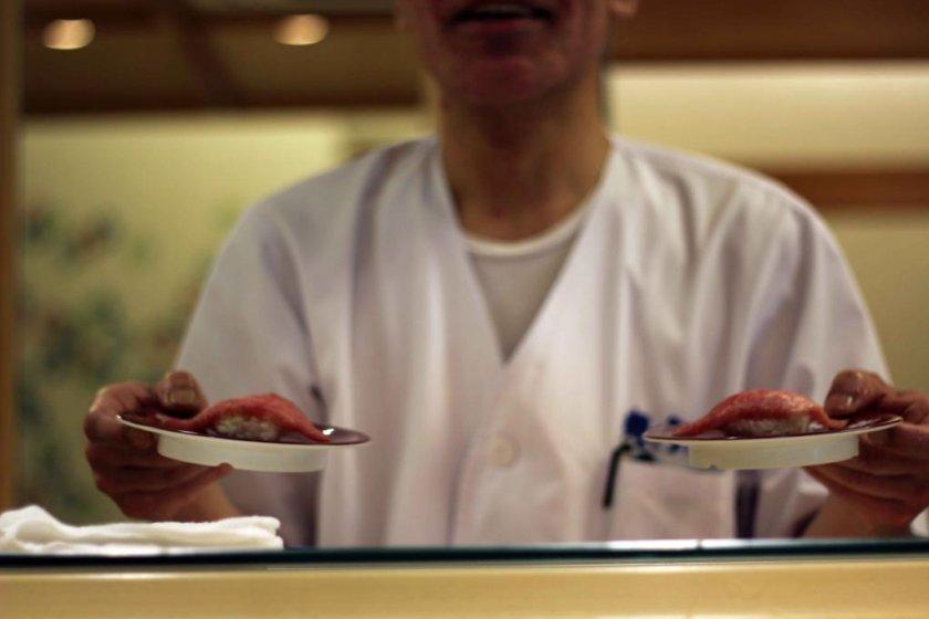 The chef hands over the otoro (fatty tuna).
