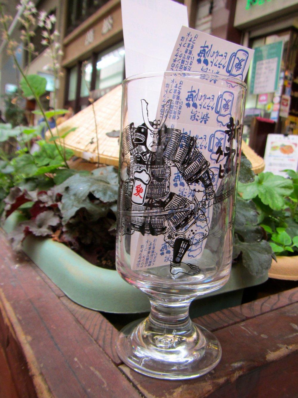 Le verre à bière souvenir et les douze tickets que l'on reçoit après avoir payé son entrée
