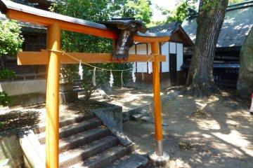 A bright orange torii gate signifies sacred ground