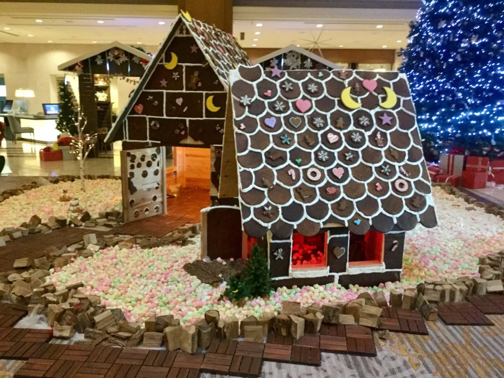 Life size gingerbread house surrounded by a marshmallow pebble, all technically edible. The gingerbread smells deliciously sweet and spicey.